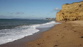 Burton Bradstock sandstone cliffs and waves crashing in to shore Dorset England uk stock video footage