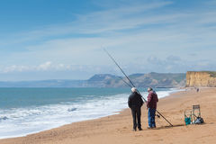 BURTON BRADSTOCK, UK - APRIL 12, 2016:  Fishermen stand on beach. With cliffs in background Royalty Free Stock Image