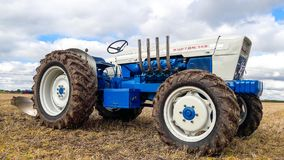 Old ford burton 148 tractor ploughing. The Burton 148 is a custom built tractor based on a Ford 5000 fitted with a Selene front axle conversion and Perkins V8 Royalty Free Stock Photo