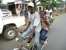 Burundi Bicycle Taxi. An enthusiastic bicycle taxi driver rides a passenger through the streets of Bujumbura, the capital of Burundi, located in East Africa Royalty Free Stock Images