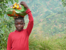 Burundi Boy with Sack on Head. A boy carries a small bundle, wrapped in fabric, on his head in the green hills outside of Bujumbura, the capital of Burundi Stock Photo