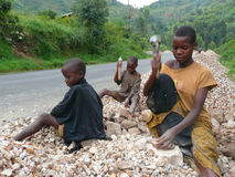 Burundi Children Break Rocks. Three children work to earn money breaking rocks to make gravel beside a road in the hills outside of Bujumbura, the capital of Stock Photography