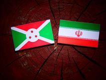 Burundi flag with Iranian flag on a tree stump isolated. Burundi flag with Iranian flag on a tree stump Royalty Free Stock Image