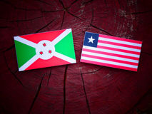Burundi flag with Liberian flag on a tree stump isolated. Burundi flag with Liberian flag on a tree stump Stock Image