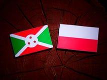 Burundi flag with Polish flag on a tree stump isolated. Burundi flag with Polish flag on a tree stump stock illustration