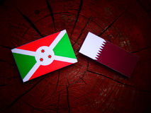 Burundi flag with Qatari flag on a tree stump isolated. Burundi flag with Qatari flag on a tree stump Stock Photo