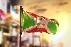 Burundi flagga mot suddig bakgrund för stad på soluppgång Backligh royaltyfria bilder