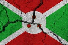 Burundi flagga på den spruckna jorden arkivfoto