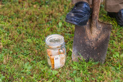 Burying a jar of money. Into the ground by digging a hole with a shovel royalty free stock photos