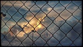 Burz chmury tworzy za drucianym ogrodzeniem Fotografia Stock