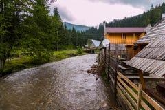 Burzowa rzeka myje banki z drewnianym domem przeciw tłu Karpackie góry pod chmurnym zdjęcia stock