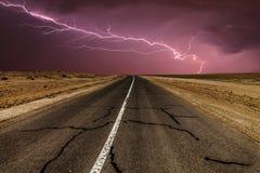 Burzowa wiejska droga przy nocą, z intensywnymi uderzeniami pioruna Obrazy Stock