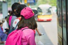 Bus aspettante della ragazza asiatica alla stazione Fotografia Stock