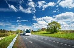 Bus auf Asphaltstraße am schönen Frühlingstag Stockbilder