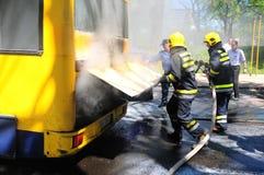 Bus auf Feuer auf der Straße Stockfotografie