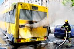 Bus auf Feuer auf der Straße mitten in dem Tag Stockbild