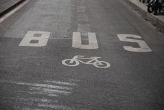 Bus & bicycle. Road signs bus and bicycle, drawn with white colour oil paint on asphalt Royalty Free Stock Images