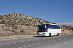 Bus blanc de touristes sur la route Photo stock