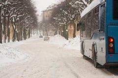 Bus blu che guida lungo le strade di città di inverno dopo le precipitazioni nevose pesanti fotografie stock