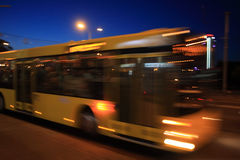 Bus blur at night. The movement of the bus with the motion blur on the street in the evening stock images