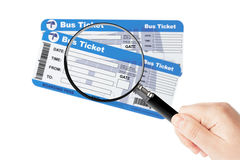Bus boarding pass tickets with magnifier glass in hand Stock Image