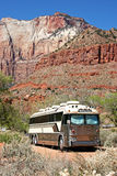 Bus Campsite. A bus converted into an RV is parked among the mountains of the desert southwest Stock Image