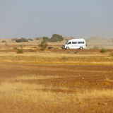 Bus carries tourists to the rocky desert. India Stock Photo