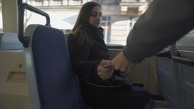 Bus conductor scanning female passenger ticket, public transportation, travel
