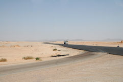 Bus  on the desert road. Of africa Stock Photos