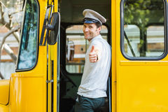 Bus driver showing thumbs up while entering in bus. Portrait of bus driver showing thumbs up while entering in bus Stock Photos