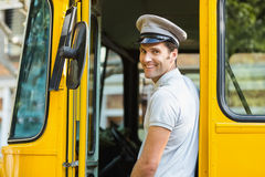 Bus driver smiling while entering in bus Stock Photo