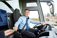 Bus driver taking ticket or card from passenger Royalty Free Stock Images