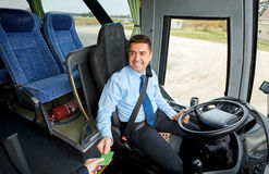 Bus driver taking ticket or card from passenger Stock Photo