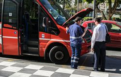 Bus drivers and mechanic arguing while the bus's bonnet is open royalty free stock photo