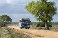 A bus drives along an unsealed dirt road on the outskirts of Panama in eastern Sri Lanka. Royalty Free Stock Image