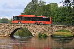 A bus drives over the Ostra Bron bridge. Karlstad, Sweden. KARLSTAD, SWEDEN – JULY 30, 2015: A bus drives over Sweden's longest arched stone bridge Ostra Royalty Free Stock Photography