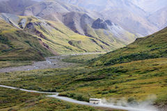 Bus drives up isolated winding dirt road in tundra between mountain valleys Stock Photos
