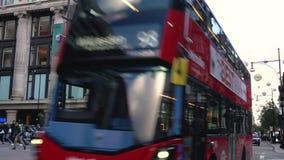 Bus e pedoni dei taxi fuori di Selfridges, via di Oxford, Londra, Inghilterra stock footage