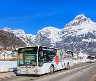 Bus on the Elgelbergerstrasse street in Engelberg, Switzerland. Engelberg, Switzerland - 9 March 2016: bus driving along the Elgelbergerstrasse street. Engelberg Royalty Free Stock Photography