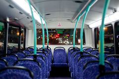 Bus empty seats. Rows of empty blue seats on a London Double Decker Bus at night Stock Photo