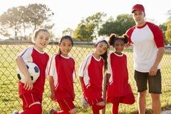 Bus en jonge meisjes in een voetbalteam die aan camera kijken stock foto