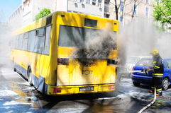 Bus on fire on the street in the middle of the day Stock Photo