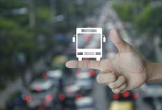 Business transportation service concept. Bus flat icon on finger over blur of rush hour with cars and road, Business transportation service concept Stock Photography