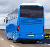 Bus geht auf Fsphalted-Land-Landstraße Stockfoto