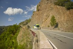 The bus goes high in the mountains above a large abyss. Walks in North Cyprus. Bus trip, Tour of North Cyprus, a dangerous road over a precipice Royalty Free Stock Images