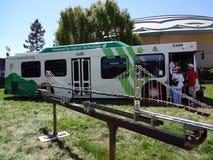 Bus ibrido di transito di Golden Gate su esposizione dietro il modello del ponte Immagini Stock Libere da Diritti