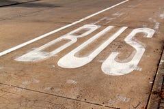 Bus lane. BUS sign on a concrete road. Traffic signs in the city. Bus lane. BUS sign on a concrete road. Traffic signs in the city Stock Image