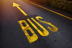 Bus lane, yellow sign with arrow. On asphalt road Royalty Free Stock Photo