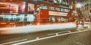 Bus a Londra con le tracce leggere alla notte fotografia stock