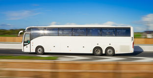 Bus in motion. Passenger bus in motion on motorway and blurred background Royalty Free Stock Photos